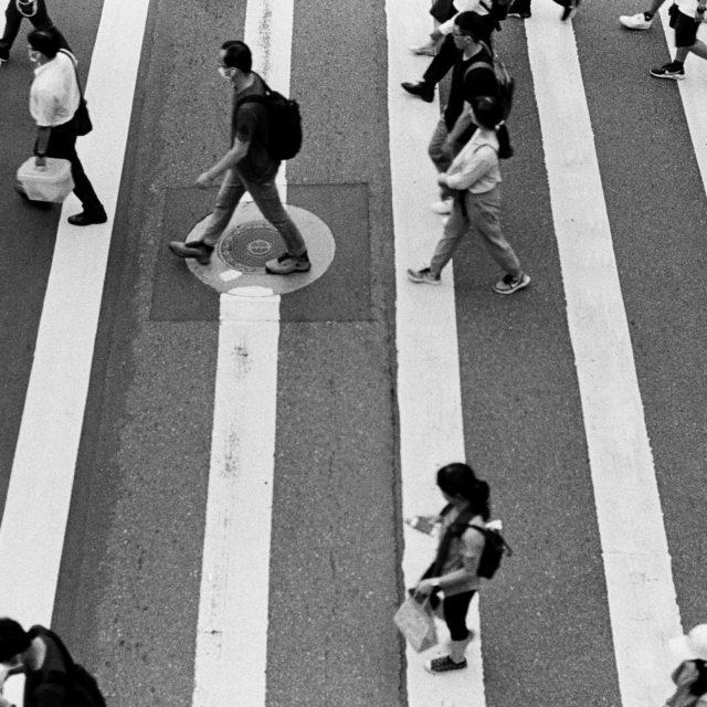 Personen überqueren einen Fussgängerstreifen