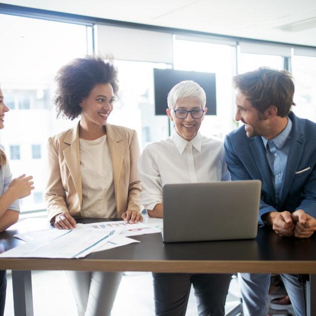 Arbeitskollegen schauen auf einen Laptop
